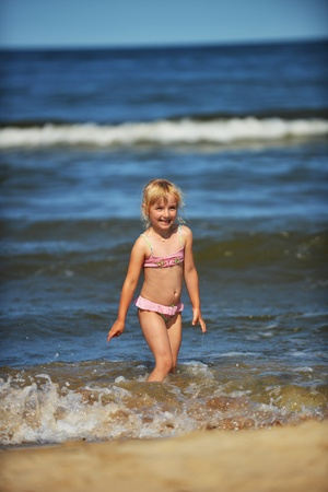 pellucid: little girl  jumping on waves. holiday at seaside Stock Photo