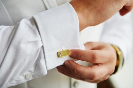 wrist cuffs: man puts cufflinks on sleeve white shirts Stock Photo