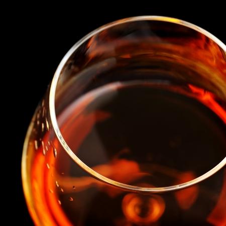 amaretto:  snifter of  brandy in  elegant  glass.  black background