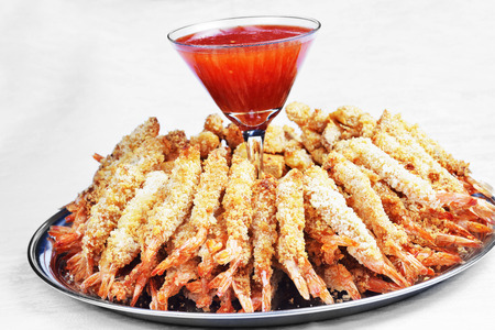 plate of sauteed prawns in breadcrumbs with sauce photo