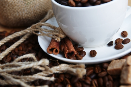 gunny: Roasted coffee beans in white cup on hessian background