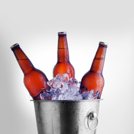 beer bucket: Three brown beer bottles in ice bucket with condensation