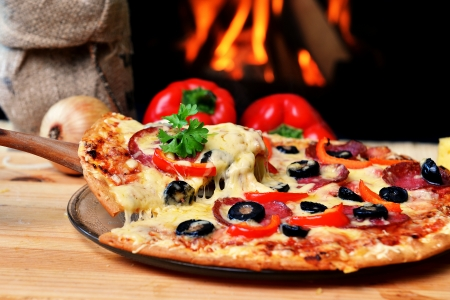 pepperoni pizza: Pizza lifting slice with pepperoni and olives Stock Photo