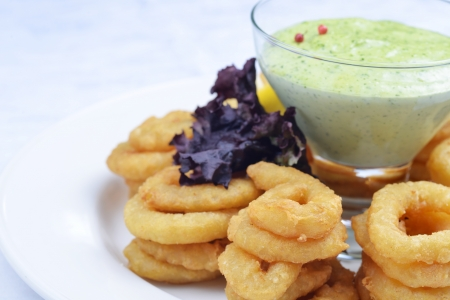 Fried onion rings with green souse photo