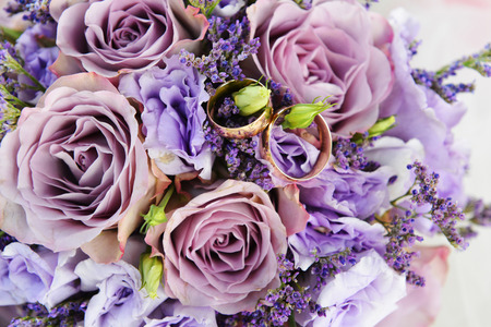 bride bouquet of purple flowers  with wedding gold rings photo