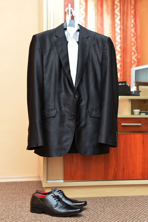 Male black suit  with necktie on rack and shoes photo
