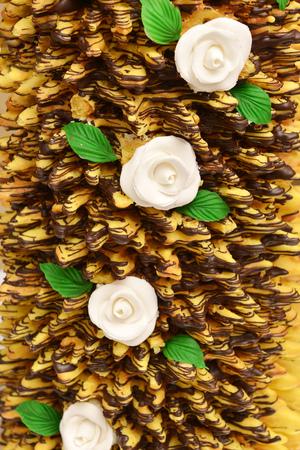 wedding cake , garnished with chocolate  and flowers of cream photo