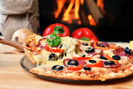 pizza oven: Pizza lifting slice with pepperoni and olives Stock Photo