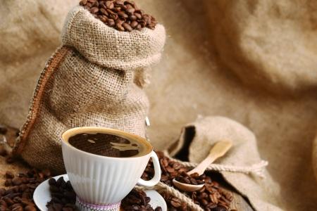 gunny: coffee beans in jute sack behind  cup of black coffee