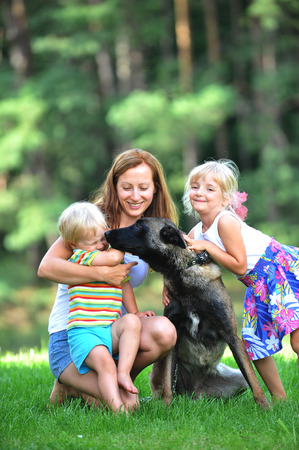 girl and her little brother playing with dog on grass photo