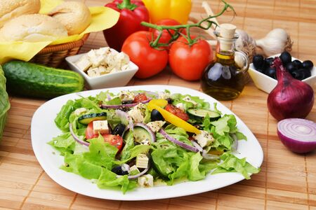 salad with feta cheese and fresh vegetables on wooden background