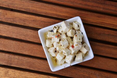 cubed: Cubed feta cheese in ceramical bowl on wooden background