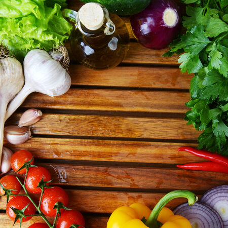 fresh vegetables and olive oil on wooden background Stock Photo - 24399612