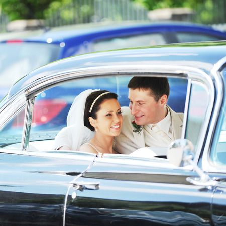 newlywed couple, groom  and bride,  in car photo