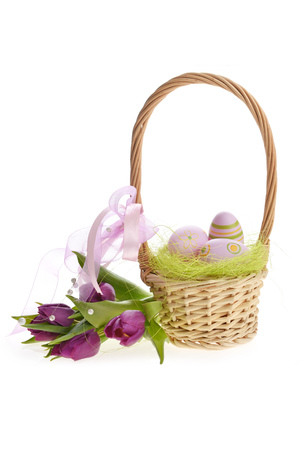 wicker basket of easter eggs with purple tulips photo