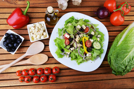 salad with feta cheese and fresh vegetables on wooden background photo