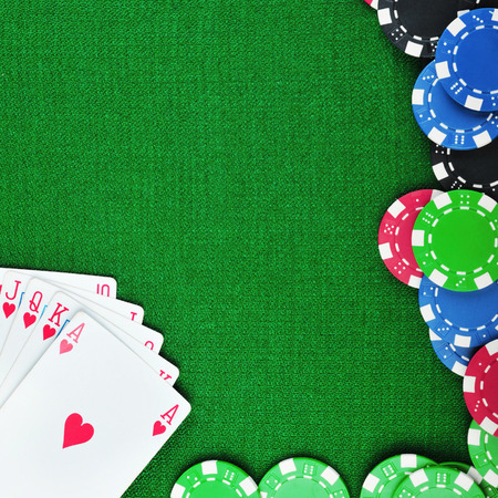 different color chips for gamblings and playing cards on green  photo