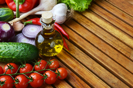 fresh vegetables and olive oil on wooden background photo
