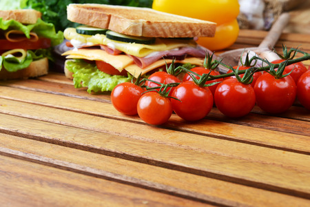 Fresh and tasty sandwich on wooden cutting board photo