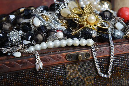earing: Wooden treasure chest with valuables. beads, necklaces and other jewelry