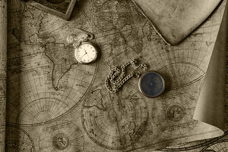 bygone: Vintage compass and a pocket watch lying on  old map