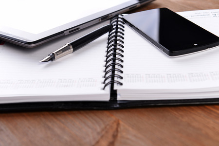 open notebook, mobile phone and black pen on white\ background