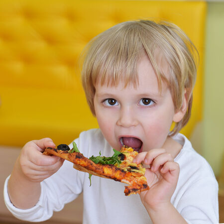 cute little boy in white tshirt eats pizza photo