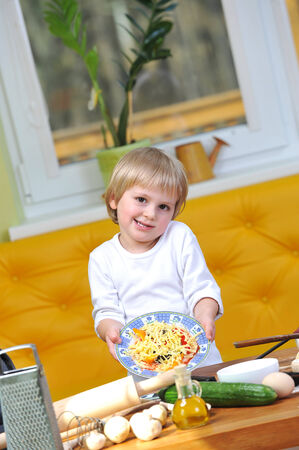 cute little boy in white tshirt shows cooked pizza photo