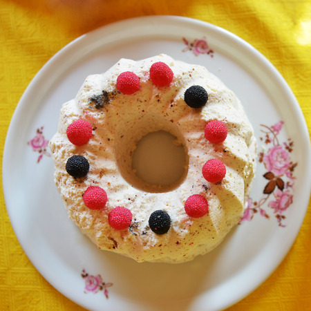 cupcake decorated with white frosting and fresh berries photo