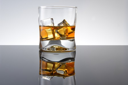 Whiskey with ice in simple glass Imagens