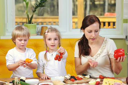 mother with children cut vegetables for pizzas photo