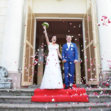 couple of newly wed showered with rose petals photo