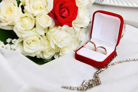 commit: wedding rings and brides  bouquet  of roses