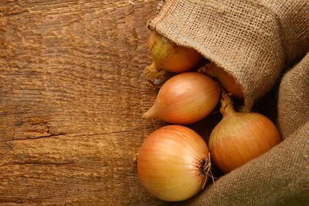 jute sack: Aprire sacco di iuta con le cipolle mature sulla tavola di legno Archivio Fotografico