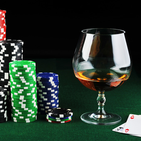 gambling counter: color chips for gamblings, drink and playing cards on green