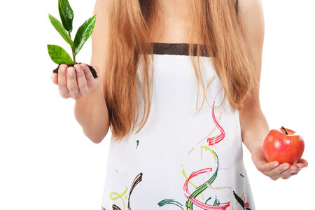 Beautiful young woman holding green sprout of tree and apple photo