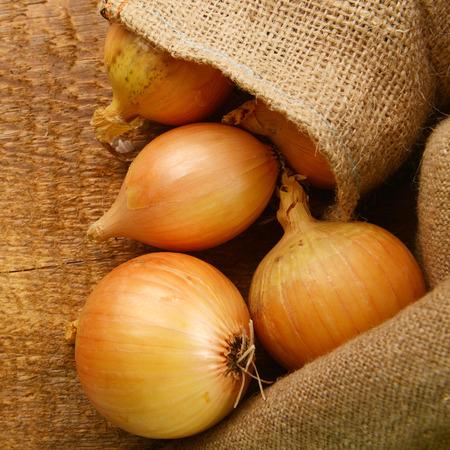 sacco juta: Aprire sacco di iuta con cipolle mature su tavola di legno Archivio Fotografico