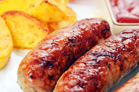 grilled meat sausages with potatoes and tomatoes photo