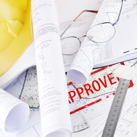 Yellow helmet and heap of project drawings photo