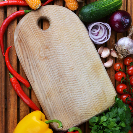 fresh vegetables and cutting board on wooden background photo