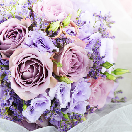 bride bouquet of purple flowers  with wedding gold rings