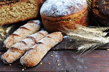 fresh bread, buns and wheat on the wooden background photo