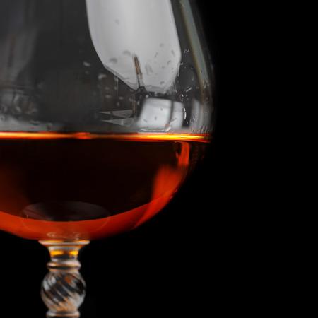 snifter of  brandy in  elegant  glass.  black background