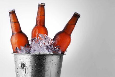 condensation: Tres botellas de cerveza de color marrón en cubo de hielo con la condensación Foto de archivo