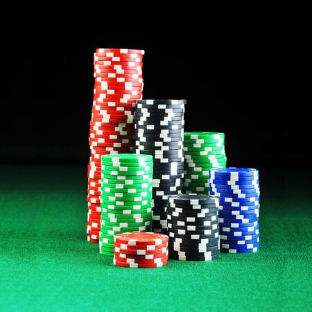 casino table: different color chips for gamblings on green background. Stock Photo