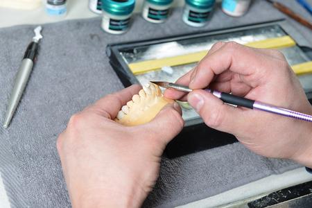 articulator: dental technician working on false teeth. table with dental tools. Stock Photo