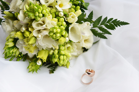 commit: wedding bouquet and rings on white background