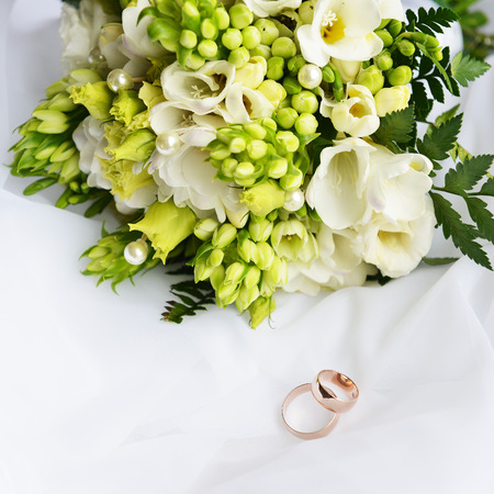 wedding bouquet and rings on white background