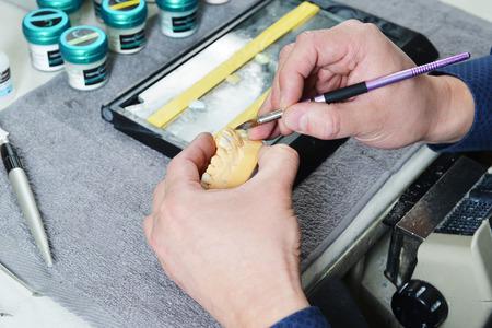 articulator: dental technician working on false teeth Stock Photo