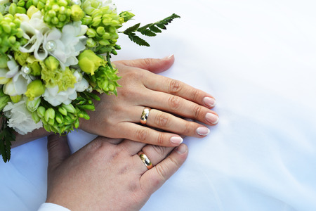newly wedded couple: Hands with wedding rings and bouquet